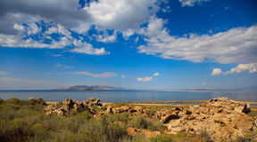 Desert Lake. Sunny afternoon lake in the high desert.  Mountain in the background, rocks in the foreground.  Blue sky, water, some clouds, nice colors Stock Photo