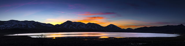 Desert lake, flooded playa at Sunset with mountain ranges and colorful clouds. Stock Photo