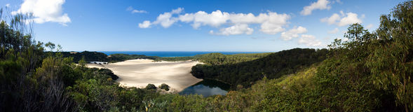 Desert Lake Panorama. Lake Wabbi in Fraser Island. Beautiful landscape panorama. Sand dunes, ocean, blue sky with rich white clouds and lake surrounded by green royalty free stock photography