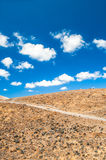 Desert land and blue sky Stock Images
