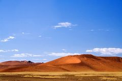 Desert landscape. Shot with red dunes and blue sky with few wispy clouds and yellow grass in the foreground in Namibia Royalty Free Stock Images