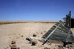 Desert landscape with broken wooden picket fence royalty free stock photo