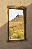 Desert Landscape in Ghost Town. Architectural Ruins of Jailhouse Window in Ghost Town of Rhyolite, Nevada with Scenic Desert Backdrop Royalty Free Stock Photos