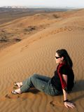Desert Landscape in Oman. Woman tourist sits on a sand dune in the desert at sunset in Oman Royalty Free Stock Image