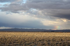 A desert landscape with a rainbow in Lancaster, California. A beautiful California desert sunset with clouds and a rainbow Stock Image