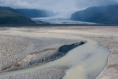 Desert landscape with river, glacier and stormy sky, Iceland Royalty Free Stock Photography