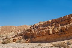 A desert landscape on a Sunny day with a blue sky shot from the side. Between the rocks stock photos