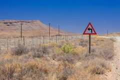 Desert landscape view of a sharp left turn sign on a dirt road i royalty free stock photos