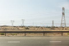 Desert beside of the main road with electricity posts and silhouette buildings in background at Dubai Stock Images