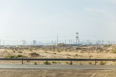 Desert beside of the main road with electricity posts and silhouette buildings in background at Dubai Royalty Free Stock Photos