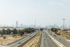 Desert beside of the main road with electricity posts and silhouette buildings in background at Dubai Royalty Free Stock Images