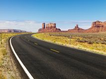 Desert mesa and road. Curve in road in scenic desert road with mesa land formations and mountains Royalty Free Stock Images