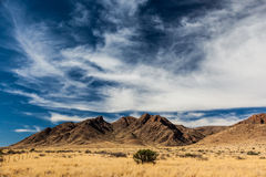 Desert mountain in Namibia. While driving North to Sussusvlei I passed this mountain in the Namibian desert. the clouds were great that day Stock Images