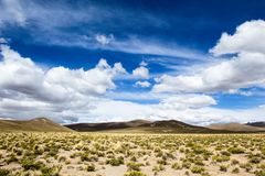 Desert and mountain over blue sky and white clouds on Altiplano,Bolivia Royalty Free Stock Image
