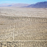 Desert and mountain range. Aerial view of remote California desert with grid pattern and mountain range in background Stock Image