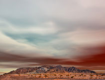 Desert mountain ravaged by mining. Colorful sky above Arizona desert mountain ravaged by mining stock image