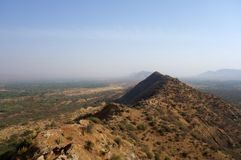 Desert Mountain Ridge in Arid Rajasthan. A view from up in the mountains of Pushkar India  looking into the vast expanse of shrub covered desert landscape Royalty Free Stock Images