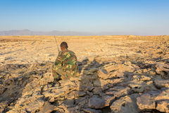 Desert near Dallol in Ethiopia with a guard sitting on a rock Stock Photos