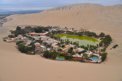 Desert oasis in Peru. Huacachina oasis in Peru is surrounded by trees and buildings forming a small village in the desert Stock Photo