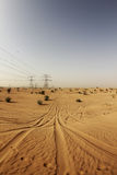 Desert Outside Of Dubai. Tyre tracks in the sand lead away into the distance in the desert expanse, just outside of Dubai stock images