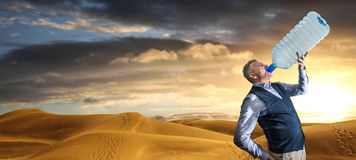 Desert panorama of the dunes at sunset with man drinking. A Desert panorama of the dunes at sunset with man drinking stock image