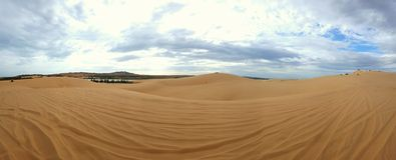 Desert Panorama. Panorama of the yellow desert sand with quad bike tracks on the dunes Royalty Free Stock Image