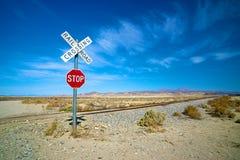 Desert Railroad Crossing and Stop Sign. Desert stop sign and railroad crossing in California's Mojave Desert Royalty Free Stock Photo