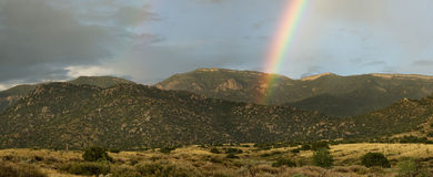 Desert rainbow and mountains Stock Images