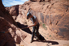 Desert Rappeling. A young man prepares to rappel into a technical canyon in northern Arizona, USA Royalty Free Stock Images