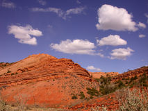 Desert Red Rocks. Gorgeous red clay hill contrasts nicely with the rich blue sky and white clouds Royalty Free Stock Photos