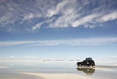 Desert Reflection. Reflection of a vehicle driving along the salt flats of Salar de Uyuni in Bolivia Royalty Free Stock Image