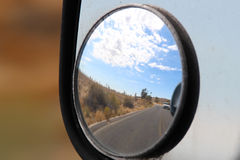 A desert reflection on the road. A distorted landscape image of a side mirror blind spot reflection of the Nevada desert of route 66 Royalty Free Stock Images