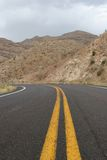 Desert road. Two lane road stretching towards the mountains Royalty Free Stock Photos