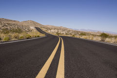 Desert road. Long stretch of winding desert road Royalty Free Stock Photography