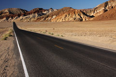 Desert road. Deserted and endless road in the desert mountains (Death Valley national park, California, USA Royalty Free Stock Image