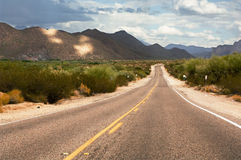 Desert road. Lonely road stretching through a desert landscape royalty free stock image