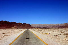 Desert Road. A long stretch of a road in the desert Stock Image