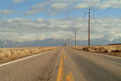 Desert road. Long desert road leading to the mountains Royalty Free Stock Image