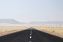 Desert Road. Lonely desert road in Namibia with heat mirage over the horizon royalty free stock photo