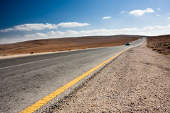 Desert road with blue car. Anonymous car driving toward the viewer on a desert road stock image