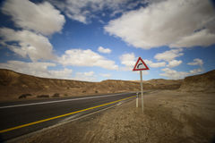 Desert road with a curve sign Royalty Free Stock Images