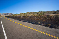 Desert Road in Cut Hillside Royalty Free Stock Photos