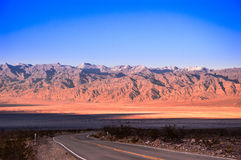 Desert road in Death Valley with mountain background. Of Death Valley Stock Images