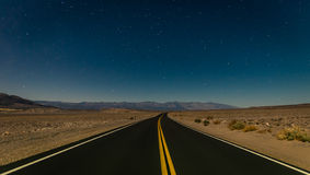 Desert road in the Death Valley by night. Under a clear sky with stars Stock Photos