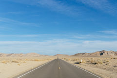 Desert road disappearing into the horizon Royalty Free Stock Photos