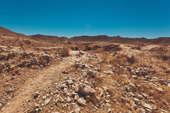Desert Road with dune and mountains in background. Desert Road full of stones with dune and mountains in background Royalty Free Stock Photos