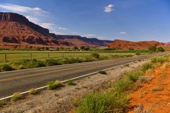 Desert road with green irrigated farmland and huge red mesa in the background. Desert road with fertile green irrigated farmland and huge red mesa in the Stock Photos