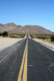 A desert road. A road in the desert only leading to the mountains with nothing else around Royalty Free Stock Photos