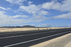 Road mountains and cloudy sky. Empty desert road on Fuerteventura Royalty Free Stock Photos