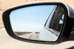 Desert road in Qatar in rear view mirror Royalty Free Stock Images
